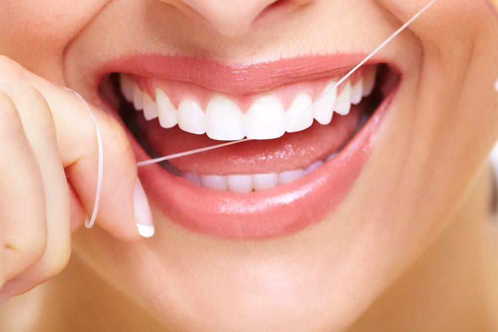 Zahnseide vor dem Zähneputzen verwenden. (Bild: kurhan / Shutterstock.com)