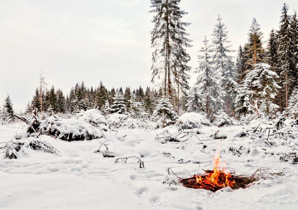 Am offenen Feuer inmitten eines verschneiten Winterwaldes. (Bild: © mangojuicy - shutterstock.com)