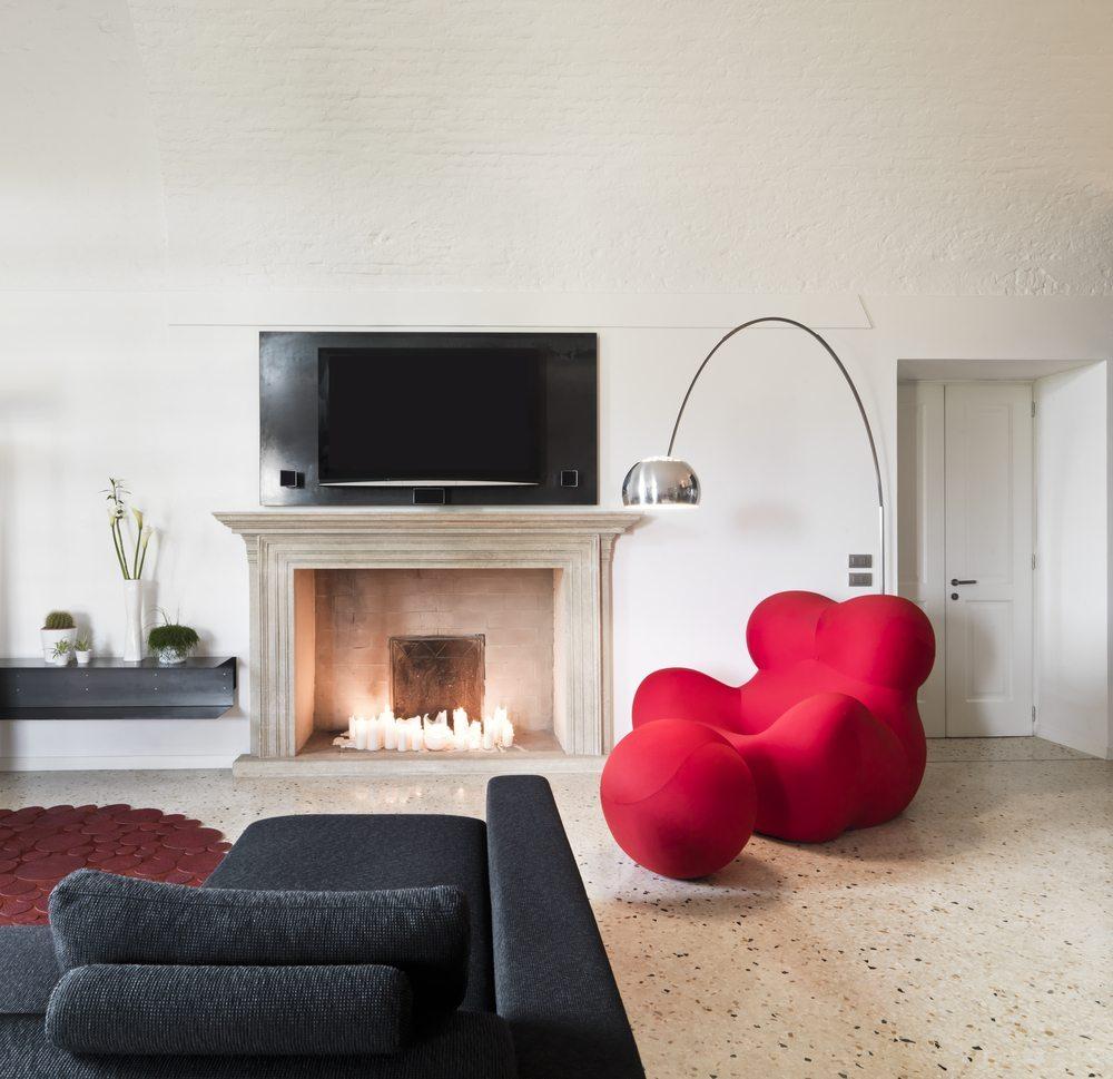 Ein roter Sessel passt wunderbar zu einer schwarzen Couch. (Bild: © adpePhoto - shutterstock.com)