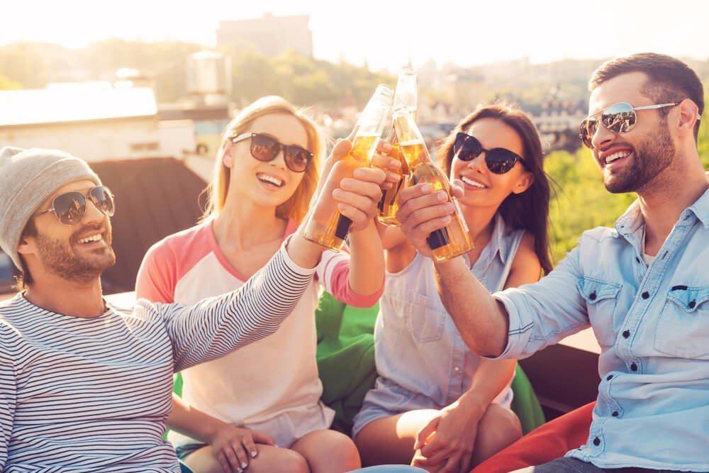Bei einem Bier mit Freunden die Sonne geniessen. (Bild: © g-stockstudio - shutterstock.com)