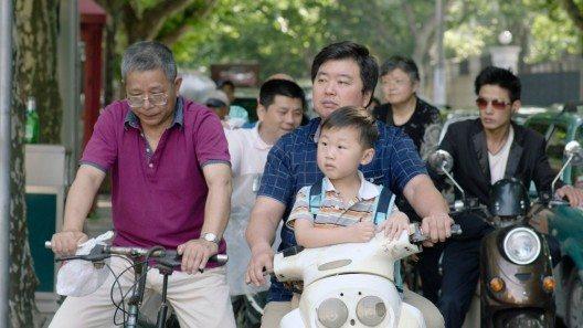 Vater und Sohn auf einem Scooter in China