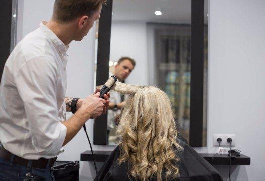 Bei einer professionellen Dauerwelle rollt der der Friseur die Haare auf Wickler auf. (Bild: © Kaspars Grinvalds - shutterstock.com)