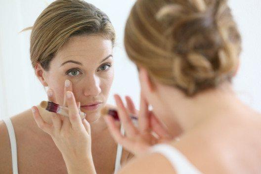 Um die dunklen Augenschatten zu neutralisieren, ist ein Concealer ideal. (Bild: Goodluz – Shutterstock.com)