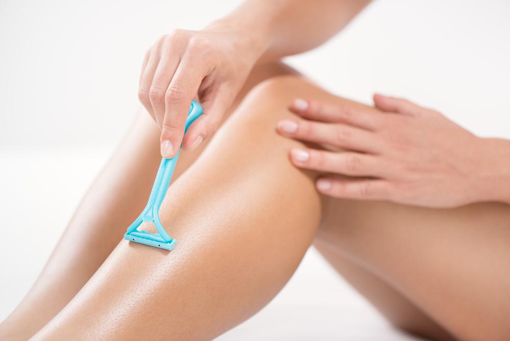 Frau rasiert das linke Bein