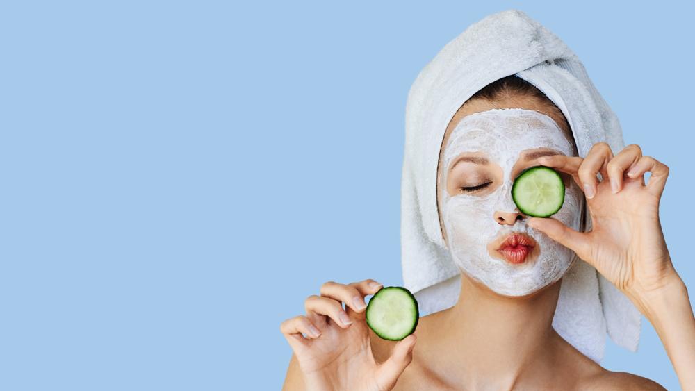 Schöne junge Frau mit Gesichtsmaske auf ihrem Gesicht, die Scheiben frischer Gurken hält.